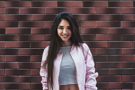 Young woman in pink jacket stading isolated on wall looking came