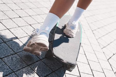 Young woman free style on the street riding skateboard on the paved road feet close-up