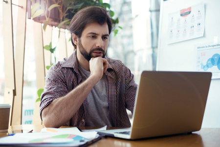 Man sitting at the table at creative stylish office looking at l
