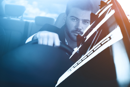 Businessman in car. Rear view of young handsome man looking on the road while driving a car