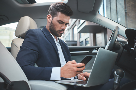 Confident businessman. Businessman with laptop in the car