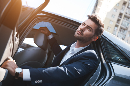 Confident businessman. Fashionable man coming out of a car