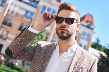 Portrait of a handsome elegant young man, model of fashion, wearing tinted sunglasses in urban background