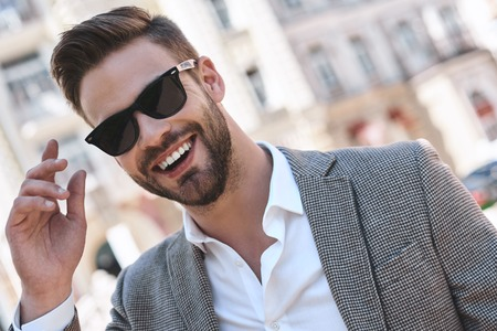 Portrait of a young handsome man, model of fashion, wearing tinted sunglasses in urban background Stock fotó