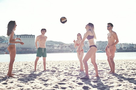 Time with friends. Group of young people playing volleyball on the beach Stock Photo