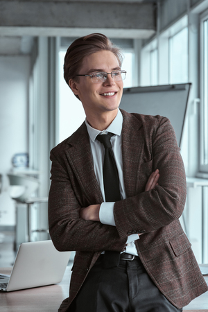 Young businessman in eyeglasses at office sitting crossed arms l Stock fotó