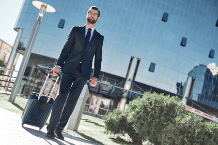 Full length of young man in full suit gesturing and shouting while walking outdoors