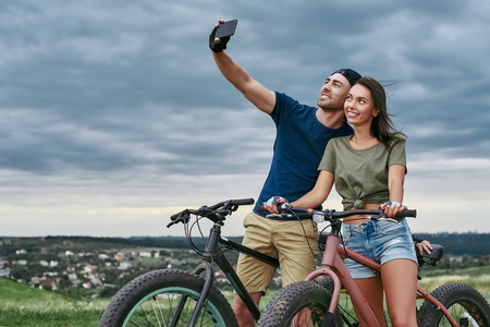 Happy couple with fatbikes taking selfie by smartphone outdoors