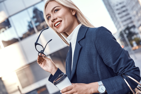 Cheerful female manager getting to work by foot drinking morning coffee to go while walking street, successful businesswoman in elegant wear enjoying sunny weather Stock Photo