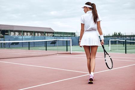 Godersi il gioco! Gambe di vista posteriore di una donna sportiva sul campo da tennis. Bella tennista femminile con racchetta da tennis e palline nel club sportivo. Moda sportiva.
