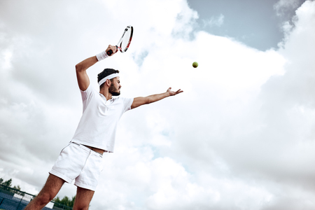 Professional tennis player playing a game of tennis on a court. He is about to hit the ball with the racket. The ball is suspended in the air. Imagens