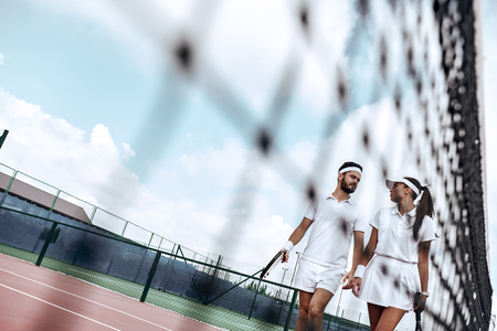 They play like a team. Beautiful young woman and man holding tennis racket and discussing set Foto de archivo - 107827288