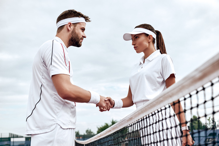Handsome man and beautiful woman are shaking their hands while playing tennis on tennis court outdoors Stock fotó