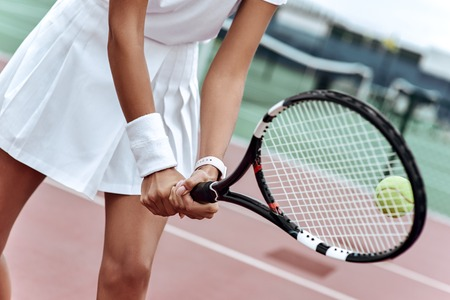 Close up of a young woman ready to hit a tennis ball, serving a ball during game.
