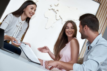 Young lovely couple sitting with manager at the travel agency office and reviewing contract for a summer vacation Stock Photo - 108836407
