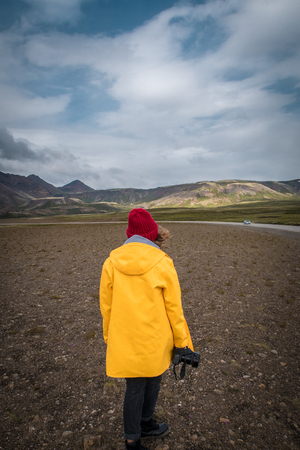 Tourist woman with camera standing near beautiful landscape. Iceland