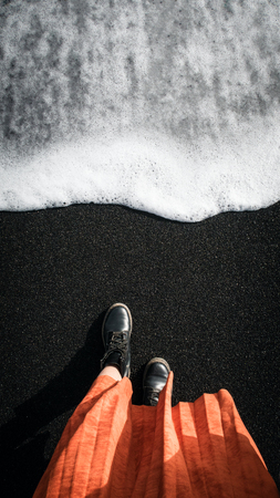 Woman in orange coat at the black volcanic sand. Icland