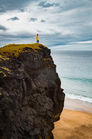 Icelandic landscape, person in yellow rain jacket. Amasing rock, Iceland.