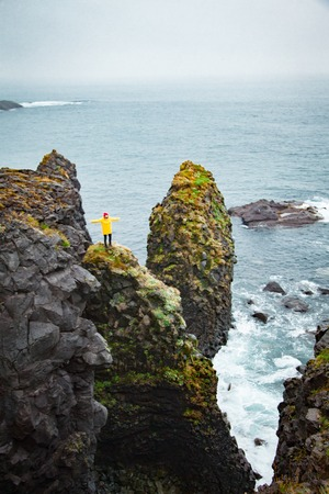 Icelandic landscape, person in yellow rain jacket. Amasing rock, Iceland.