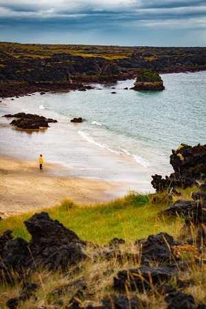 Iclandic landscape sea shore with a man in yellow coat