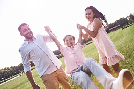 Bonding. Family of three walking on grassy field holding son up