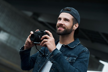 Photography hobby. Young stylish man standing on city street taking photos on camera looking forward smiling joyful close-up Foto de archivo - 108748465