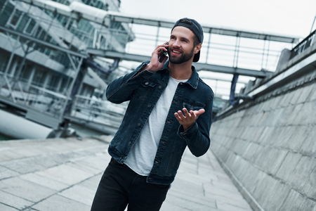 Outdoors leisure. Young stylish man walking on city street talking with friend on smartphone smiling cheerful