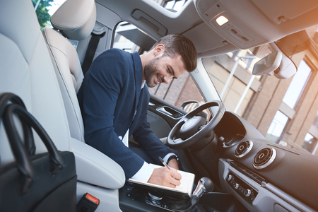 Businessman writes notes in the car, getting ready for a meeting