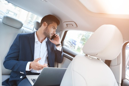 A young man in the car discussing business matters by phone Stok Fotoğraf