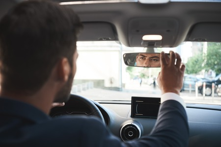 Handsome bisnessman behind the wheel adjusting rear view mirror. Imagens