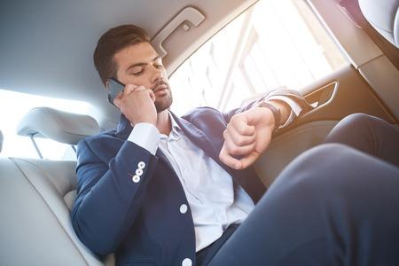 Late for a meeting. The lack of time. Young man in suit sitting in the car looking at watch and talking on the phone