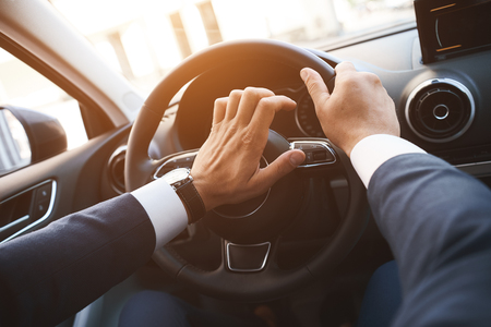 Close-up of a man driving a car with a hand on a horn button. Sunset filter Stockfoto