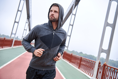 Morning workout. Close up of young man in sports clothing exercising while jogging on the bridge outdoors Stock fotó