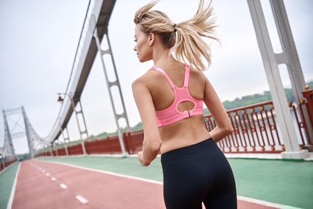 Morning workout. Close up of young womanin sports clothing exercising while jogging on the bridge outdoors Stock fotó