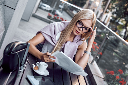Attractive business woman reading newspapers at city cafe