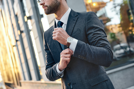 Cropped profile portrait of a successful young bearded guy in suit and glasses. So stylish and nerdy. Outdoors on a sunny street, fixing his cuffs Stock Photo