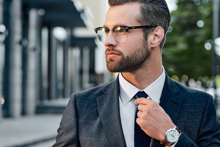 Close-up handsome and successful man in spectacles and in an expensive suit. He is in a white shirt with a tie. The man straightens his tie, his face unshaven. Stock Photo