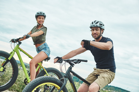 What time is it. Young couple are cycling on fatbikes and in helmets. Close up Stock fotó