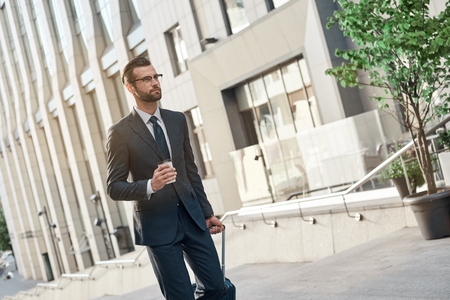 A young businessman spectacled climbs the stairs with coffe and suitcase Imagens