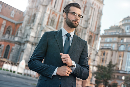 Close up profile portrait of a successful young bearded guy in suit and glasses. So stylish and nerdy. Outdoors on a sunny street, fixing his cuffs Stock Photo