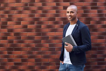 Desarrollo cerebral. Chico joven de pie en la pared sosteniendo el libro mirando a un lado sonriendo alegre Foto de archivo