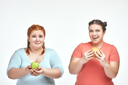Funny picture of amusing chubby women on white background. One woman holding a sandwich, the other holding an apple.