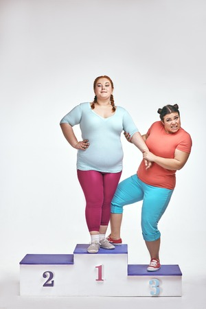 Overweight women are standing on a winners pedestal isolated on white background and argue