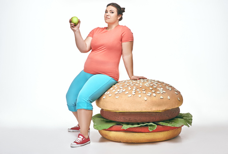 Funny picture of brunette, bearded, plump woman on white background. Woman wearing sportswear. She laid crouched on a huge sandwich Banque d'images - 117617276