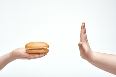 In picture one person offers sandwich another, but the person refuses.