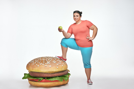 Funny picture of brunette, bearded, plump woman on white background. Woman wearing sportswear. She put her leg to a huge sandwich