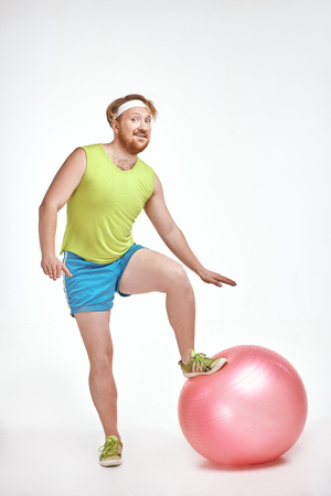 Funny picture of red haired, bearded, plump man on white background. Man wearing sportswear. Man put his leg to a fitness ball