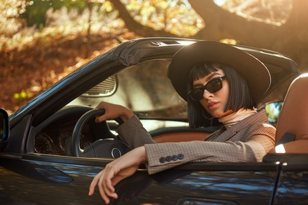 Sexy lady in the roofless car. Stylish woman is wearing sunglasses and black hat. She had fashion haircut. Autumn season. 写真素材
