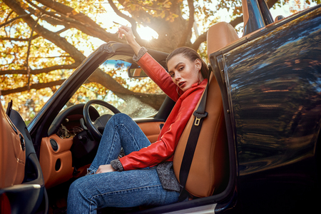 Beautiful girl in the roofless car. Autumn season, red coat and jeans, stylish sunglasses on head. Skin salon Stock Photo