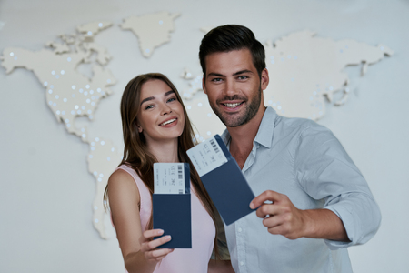 Portrait of joyful glad couple holding passport with flying tickets in hands pointing with forefinger looking at camera on map background 写真素材